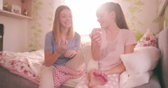 Adolescent friends sharing nail varnish in a colourful bedroom Stock Footage