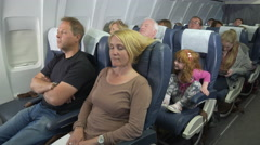 Naughty kid on flight pulling hair of passenger sitting in front of her Stock Footage