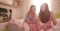 Smiling teen girl painting her friend's toenails in a bedroom Stock Footage