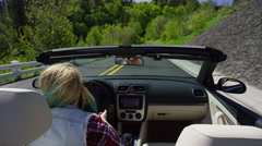 Woman driving convertible car on curvy road Stock Footage