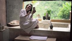 Young woman taking selfie with cellphone sitting on the edge of bathtub  HD Stock Footage