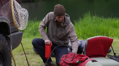 Fly fisherman pumping up float tube - stock footage