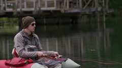 Fly fisherman fishing from float tube - stock footage