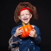 Little boy in a pirate costume for Halloween on a black background - stock photo