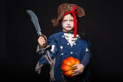 young boy dressed in a pirate outfit, playing trick or treat for Halloween - stock photo