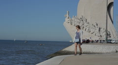 Lisbon, Portugal - September 2015: young girl is walking near the Monument to Stock Footage