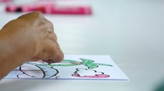 Adult person painting on the paper with crayon Stock Footage