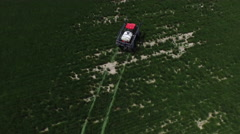 Aerial shot of tractor spraying grass seed farm Stock Footage