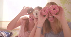 Adolescent girls with colourful doughnuts over their eyes - stock footage