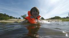 Boy in water in life jacket in Stockholm archipelago - stock footage