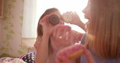 Girls having a pyjama party with sugary donuts - stock footage