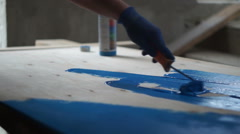 Painting workshop. Carpenter paint wooden surface with blue.  Stock Footage