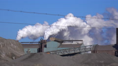 Global warming is suggested by shots of a steel mill belching smoke into the - stock footage