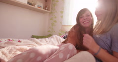 Adolescent girls laughing out loud at a pyjama party - stock footage