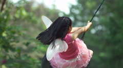 Girl in fairy princess costume on tire swing - stock footage