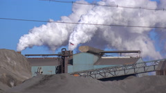 Global warming is suggested by shots of a steel mill belching smoke into the Stock Footage