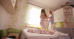 Girls wearing pyjamas jumping wildly on a bed together - stock footage