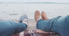 POV: Couple feet on the beach near water playing footsie. 4K Slow Motion. Stock Footage