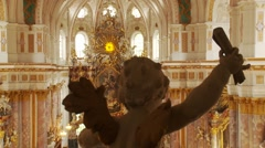 Church cherub statue holds parchment in ornate baroque cathedral, altar behind - stock footage