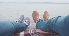 POV: Couple holding Hands. Slow Motion 4K. Feet in modern shoes on lake beach - stock footage