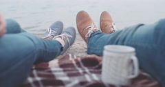 POV: Couple relaxing on the Beach. Woman taking a cup with drink Slow Motion 4K Stock Footage