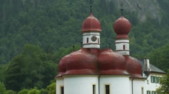 Konigssee lakeside church in Bavarian Alps, boat view, zoom out Stock Footage