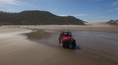 Stock Video Footage of Aerial shot of 4x4 off road vehicle driving on beach