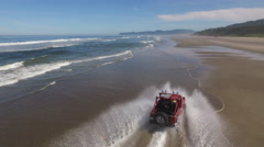 Aerial shot of 4x4 off road vehicle driving on beach Stock Footage
