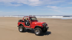 Couple driving 4x4 off road vehicle driving on beach Stock Footage