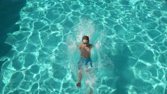 Boy splashing into pool in slow motion, shot on Phantom Flex 4K Stock Footage