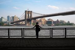 Woman Stands Looking at Brooklyn Bridge in New York City Stock Photos