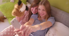 Adolescent girls taking a silly selfie in a sunlit bedroom - stock footage