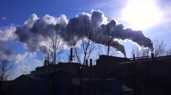 Global warming is suggested by shots of a steel mill belching smoke into the air Stock Footage