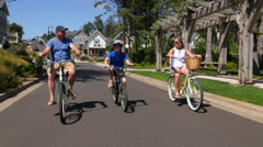Family riding bicycles together in coastal vacation community Stock Footage