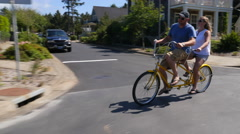 Couple riding tandem bicycle together in coastal vacation community Stock Footage