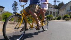 Couple riding tandem bicycle together in coastal vacation community - stock footage