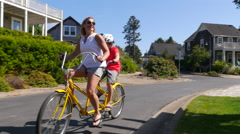 Mother and son riding tandem bicycle together in coastal vacation community Stock Footage