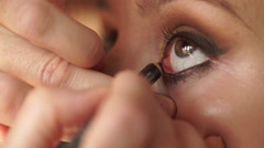 Two women. Makeup artist applying black eye liner to model eye. Stock Footage