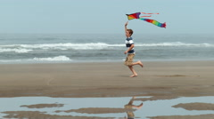 Boy running with kite at beach, slow motion Stock Footage