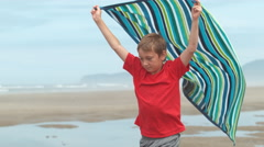 Boy running with towel at beach, slow motion - stock footage
