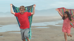 Kids running with towels at beach, slow motion - stock footage
