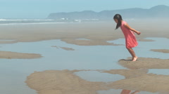Girl jumping into puddle at beach, slow motion Stock Footage