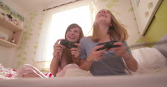 Girls laughing out loud on bed with computer game controls - stock footage