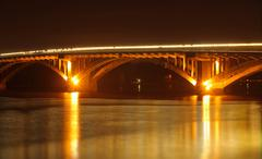 Reflection of bridge illumination in water of city river at night - stock photo