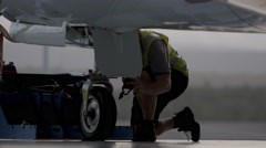 Stock Video Footage of Aircraft engineer working on Private Jet landing gear