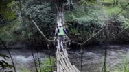 Stock Video Footage of Hiker crossing dangerous bridge