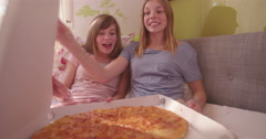 Happy teenagers opening a large pizza box in their bedroom Stock Footage
