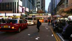 Pedestrian walk crossing dark street, taxi car drive beside, bright shops ahead Stock Footage