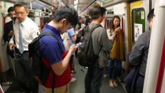 People within moving metro train, boy looking smart phone, man pass by Stock Footage