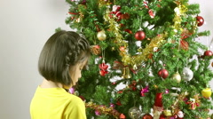 HD footage of Young Asian girl putting ornament on Christmas tree Stock Footage